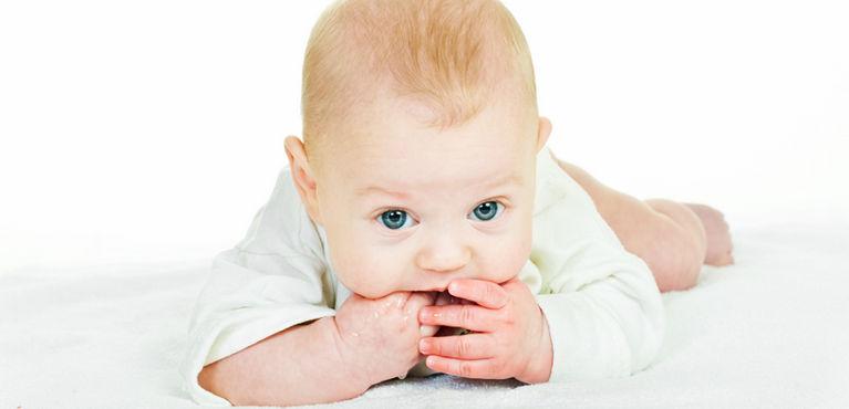 ребенок лежит на животе и сосет пальцы
