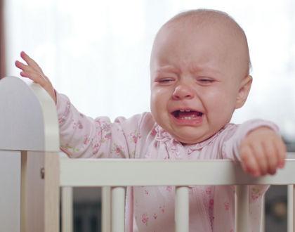 ребенок плачет стоя в кроватке