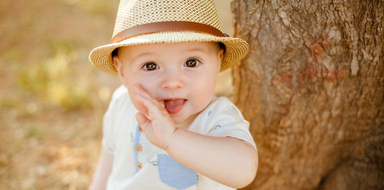 ребенок сосет палец в шляпе