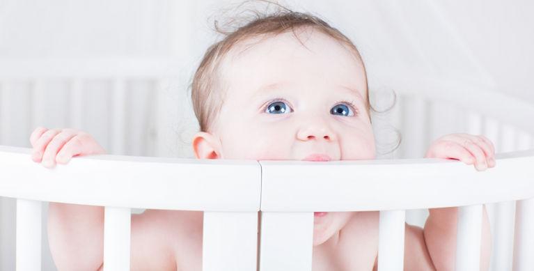 ребенок стоит в кроватке и грызет бортик