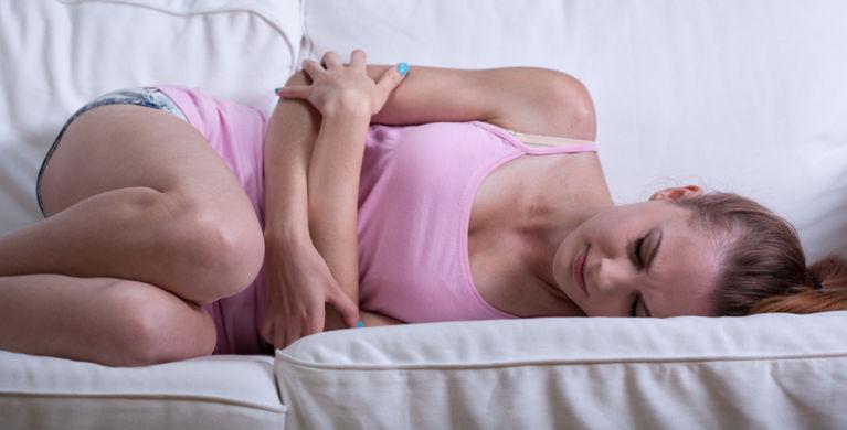 женщина держится за живот лежа на диване
