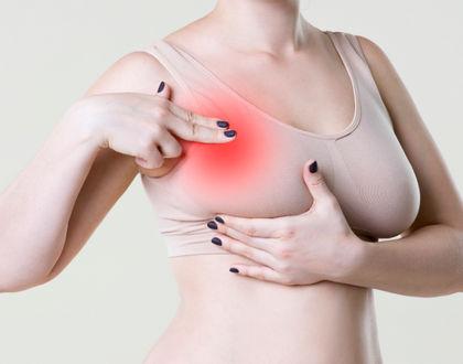 женщина ощупывает грудь в бюстгальтере
