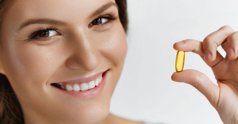 женщина с капсулой в руке улыбается