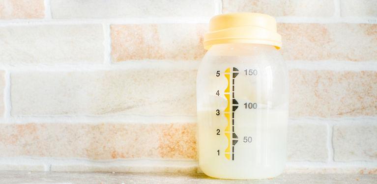 бутылочка с грудным молоком на фоне кирпичной стены