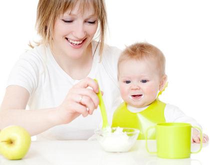 мама кормит ребенка и улыбается