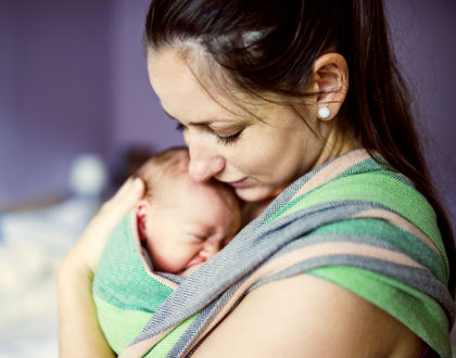 мама прижимает к себе ребенка в слинге