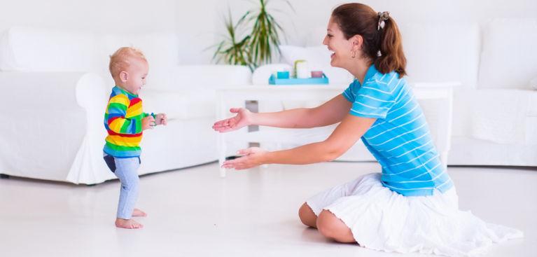 ребенок делает первый шаг к маме