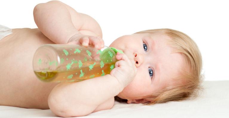 ребенок лежит на спине и пьет чай из бутылочки