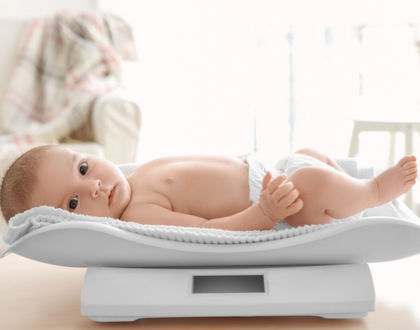 ребенок на весах лежит в памперсе