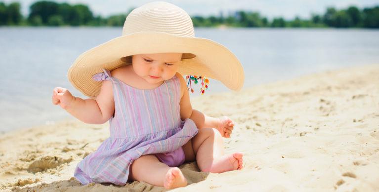 ребенок сидит на песке в шляпе
