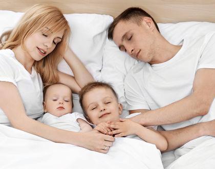 родители спят с детьми и улыбаются