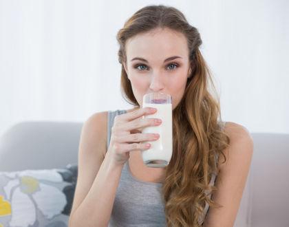 женщина со стаканом молока сидит на диване