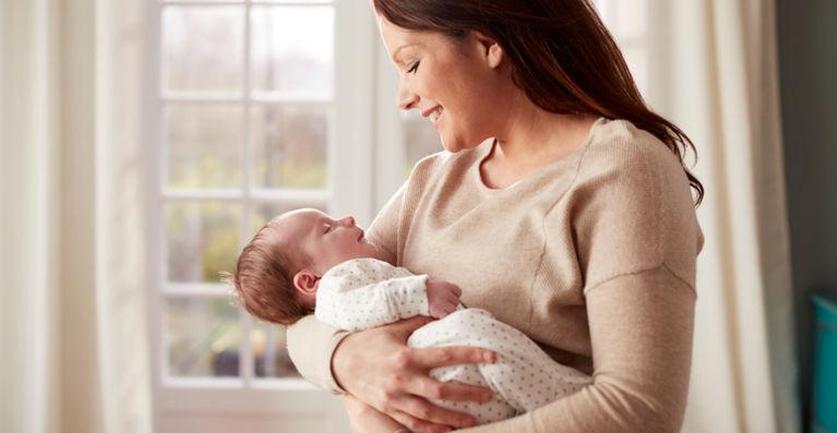 мама держит ребенка на руках и улыбается