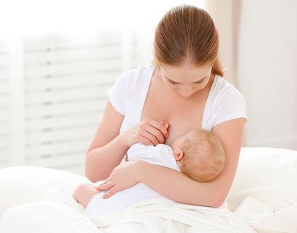 мама кормит ребенка грудью сидя на кровати