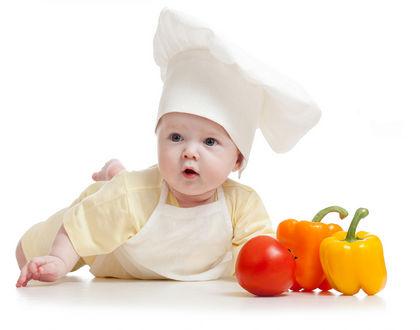 ребенок лежит на животе в колпаке и с овощами