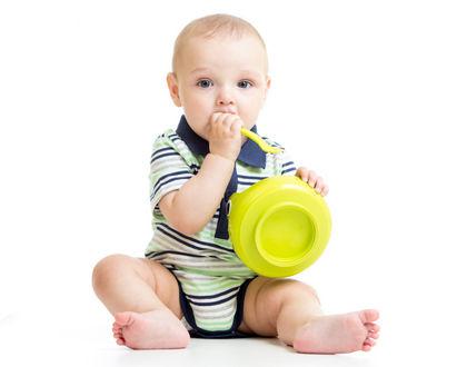 ребенок сидит с тарелкой и ложкой во рту