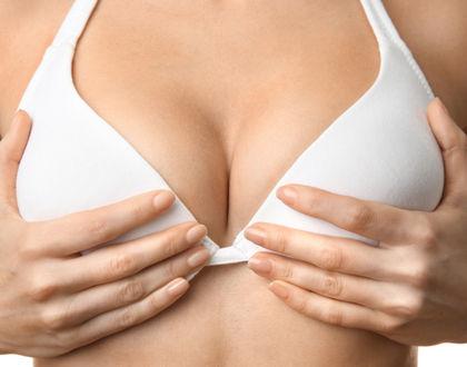 женщина держит руками грудь в белом бюстгальтере