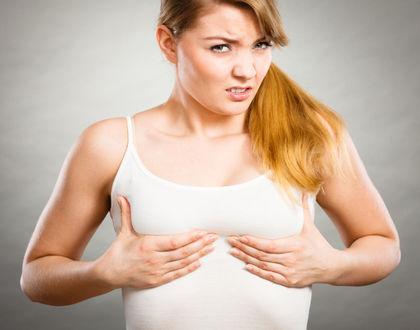 женщина поддерживает грудь руками и испытывает боль