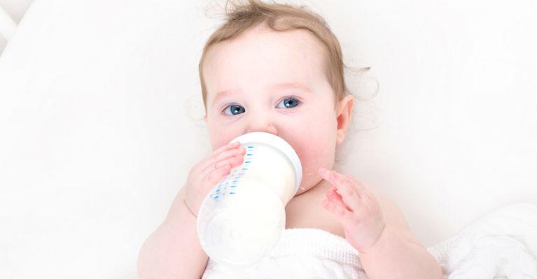 ребенок пьет из бутылоки лежа в кроватке