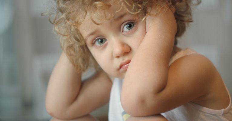 кудрявый ребенок закрыл уши руками и грустит