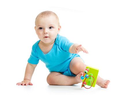 ребенок с игрушкой сидит и тянется