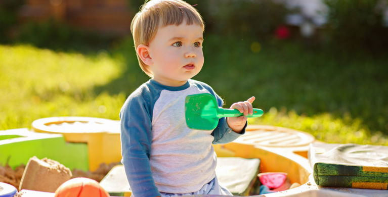ребенок в песочнице стоит с лопаткой в руках