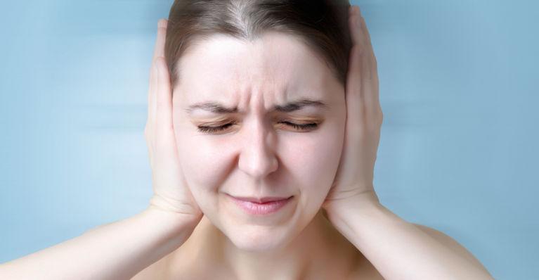 женщина держится за уши