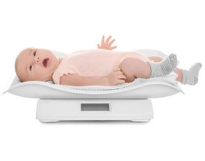 ребенок на весах лежит