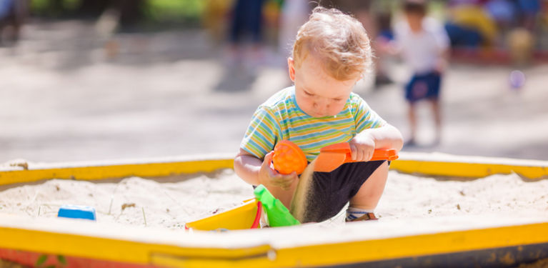 ребенок в песочнице играет один