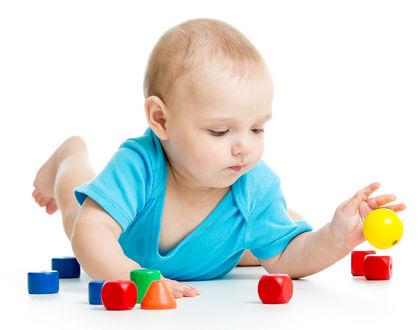 ребенок на животе играет с кубиками