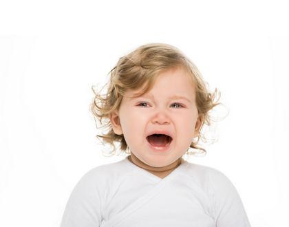 ребенок плачет в белой одежде