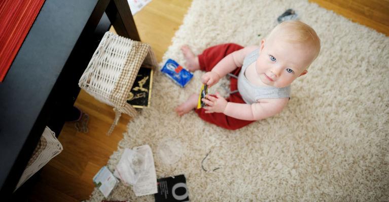 ребенок сидит на полу и играет с мамиными вещами