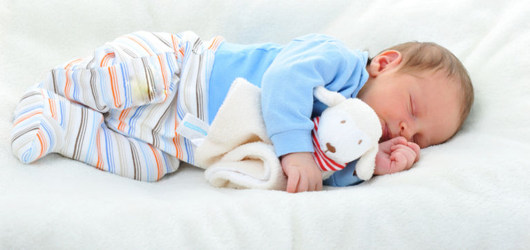 ребенок спит на боку с игрушкой