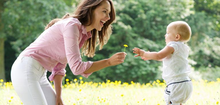 мама дает цветок ребенку и улыбается