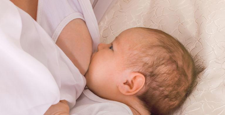 мама кормит грудью младенца в бюстгальтере