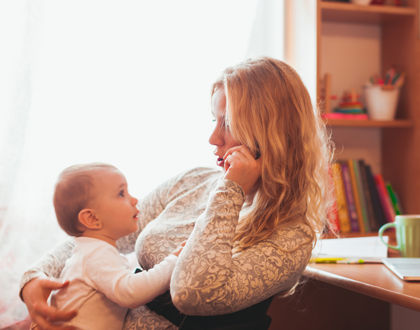 мама разговаривает по телефону и держит ребенка