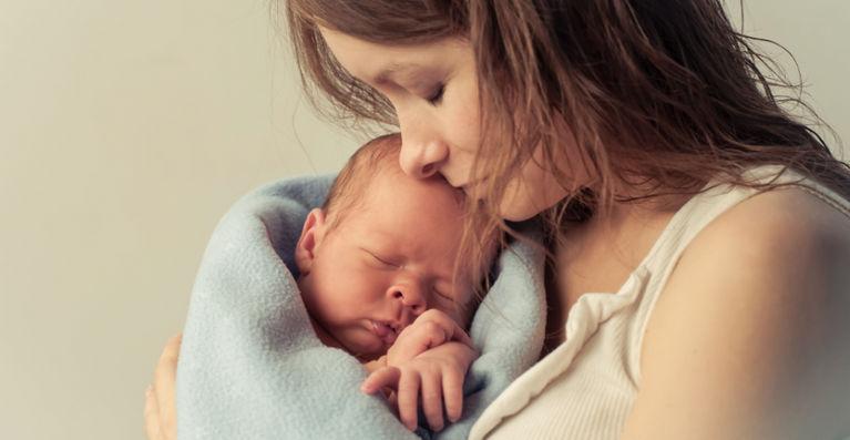 новорожденный спит на руках у мамы