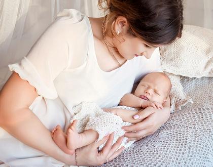 мама перекладывает ребенка на кровать