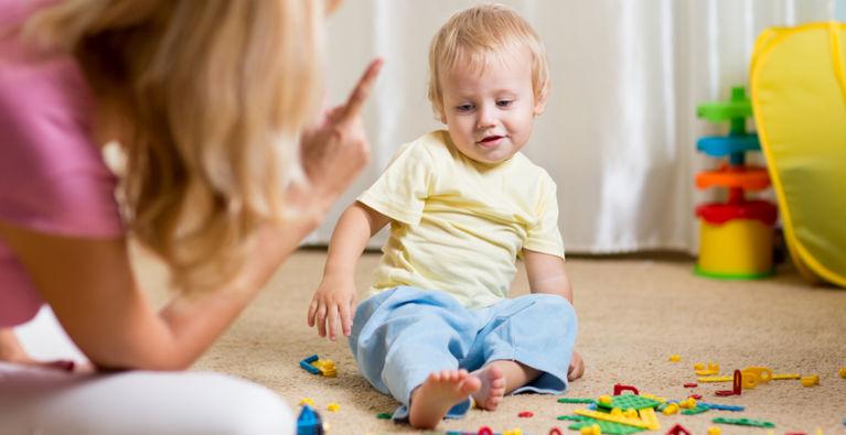 мама ругает ребенка играющего на полу