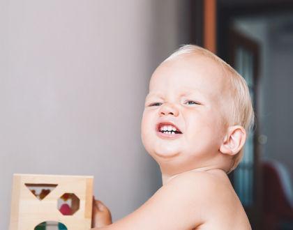 недовольный ребенок держит игрушку