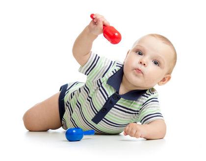 ребенок лежит на животе и поднял руку с игрушкой