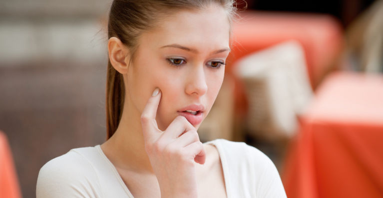 женщина думает и трогает лицо рукой
