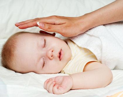 мама держит руку над ребенком спящим