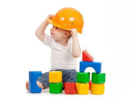 ребенок сидит в каске с кубиками