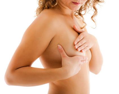 женщина осматривает свою грудь руками