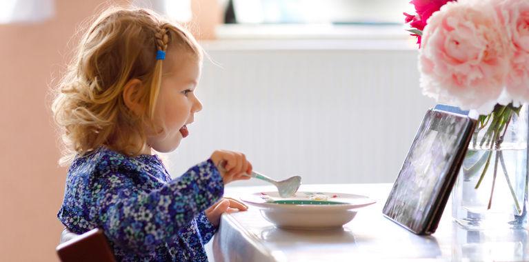ребенок кушает и смотрит планшет