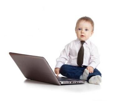 ребенок с ноутбуком сидит на полу