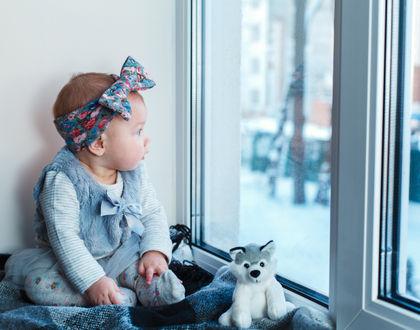 Девочка сидит у окна