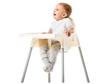 ребенок сидит на стульчике для кормления и улыбается