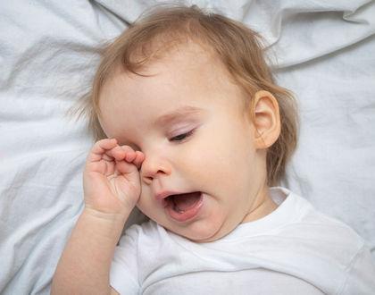 ребенок зевает и трет глазки